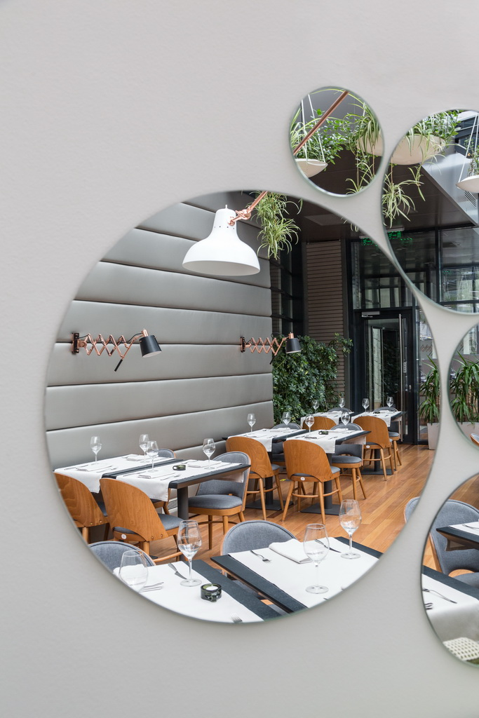 round mirrors in dining room,wall mirrors in restaurants,designer restaurant tables and chairs,designer lighting for restaurant,indoor garden ideas,