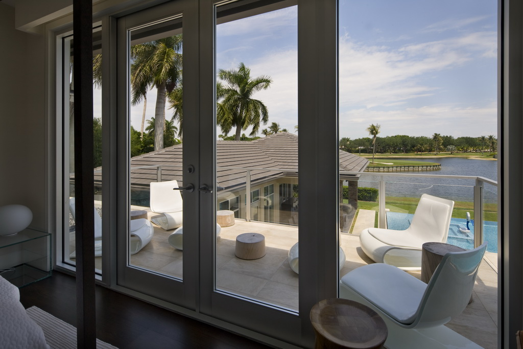 luxury home with swimming pool,high end florida real estate,white outdoor lounge chairs,luxury home balcony design,beautiful view from the bedroom,