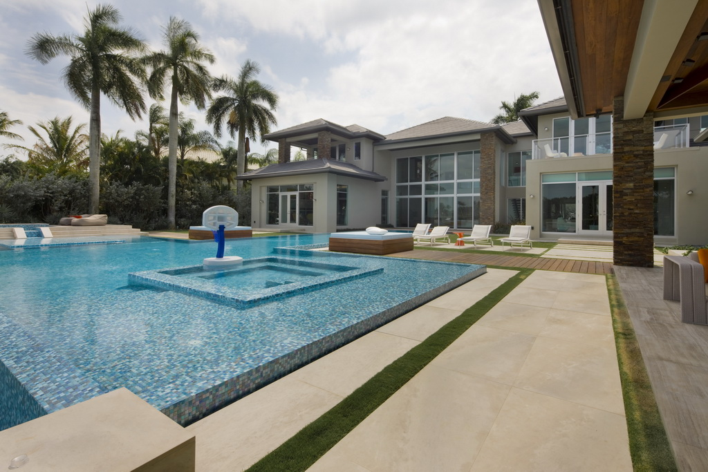 luxury home with swimming pool,high end florida real estate,white outdoor lounge chairs,luxury home terrace design,beautiful view from the bedroom,