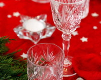star decor on holiday table,holiday candle centerpieces,festive holiday table settings,crystal glasses holidays,red holiday tablecloth,