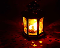 holiday lantern centerpiece,star decor on holiday table,candle in glass lantern,stars scattered on the table,holiday candle centerpieces,