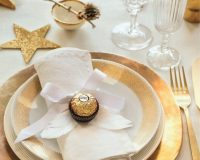 gold star table decorations,luxury holiday table ideas for families,cloth napkin folding Christmas,white and gold holiday table,ferrero rocher wedding table decorations,