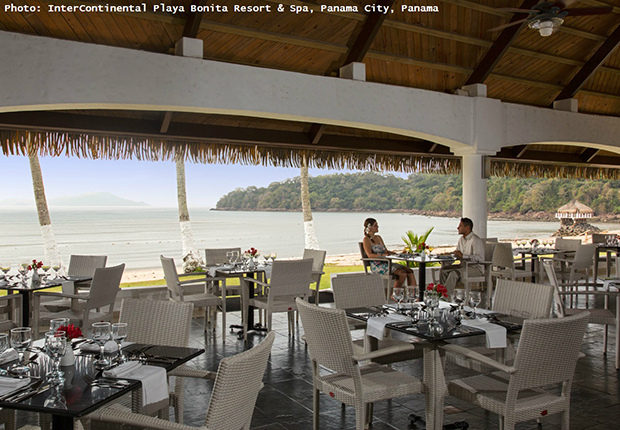 a couple sitting in a restaurant,romantic travel destinations,white restaurant furniture,panama city hotels on the beach,romantic couple photos,