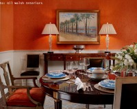 orange feature wall dining room,luxury dining room design,wooden dining table and chairs,dining table arrangement ideas,blue white decorative plates,