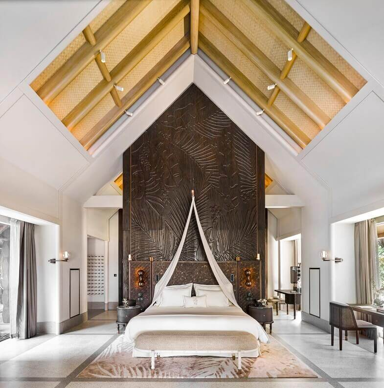 joali maldives beach villa bedroom,hand carved wooden wall panels,white and brown bedroom ideas,tropical style hotel room designs,high ceiling bedroom ideas,