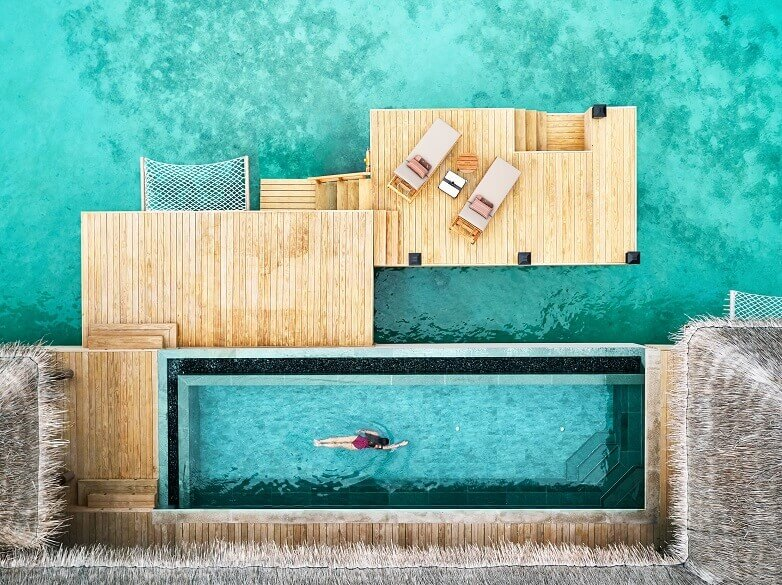 swimming pool by the sea,woman swimming in pool,joali maldives water villa,lounge chairs by the pool,wooden resort design,