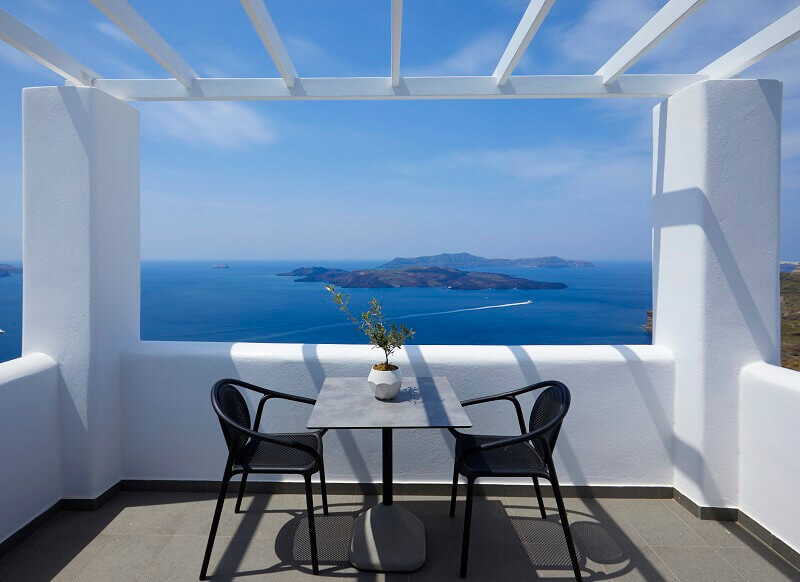 small luxury hotels europe,terrace with a sea view santorini,designer outdoor chairs dining,petit palace suites hotel santorini,luxury hotel terrace restaurant,