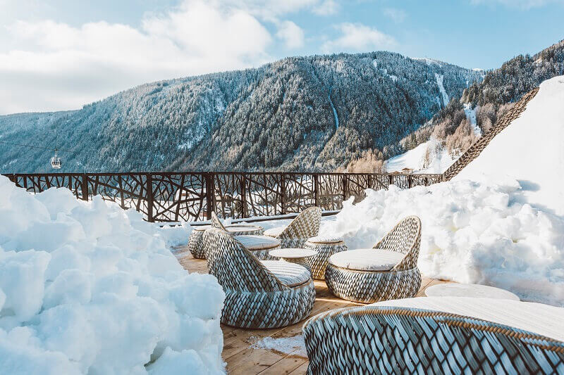 romantic getaways in the snow,design hotels mountain,sitting on a snowy terrace,hotel roof terrace south tyrol,terrace fence design inspired by tree branches,