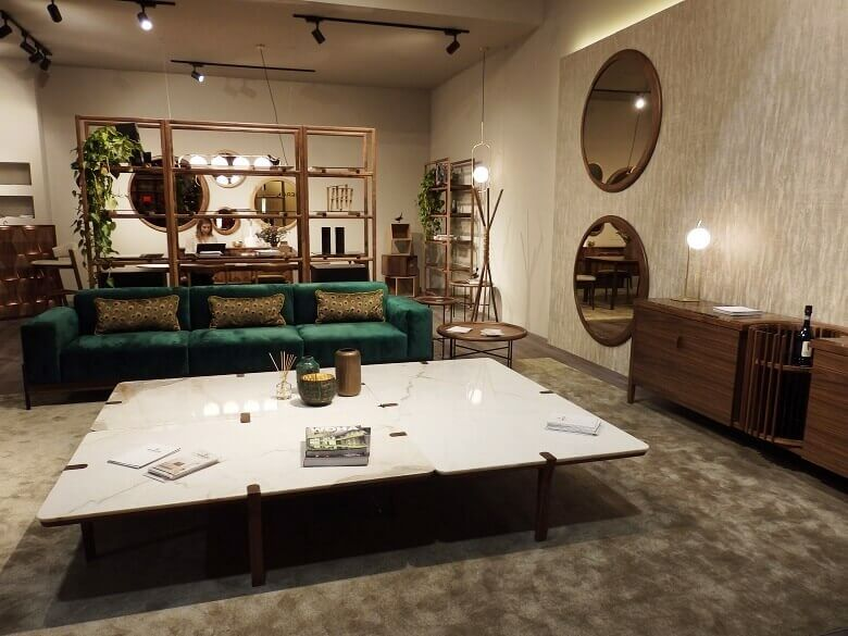 modern designer furniture wood,large wooden bookshelf,luxury green velvet sofa,round mirrors with wooden frame,wood tones and green decorating,