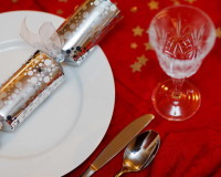 Christmas table ideas red and silver,festive holiday table settings,silver holiday table decor,crystal wine glasses,silver stars red tablecloth,