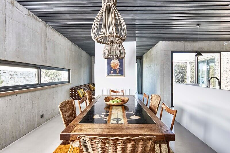 mediterranean dining room ideas,concrete walls interior design,ceramic and wood dining table,natural materials in dining room interior design,wicker ceiling light shade,
