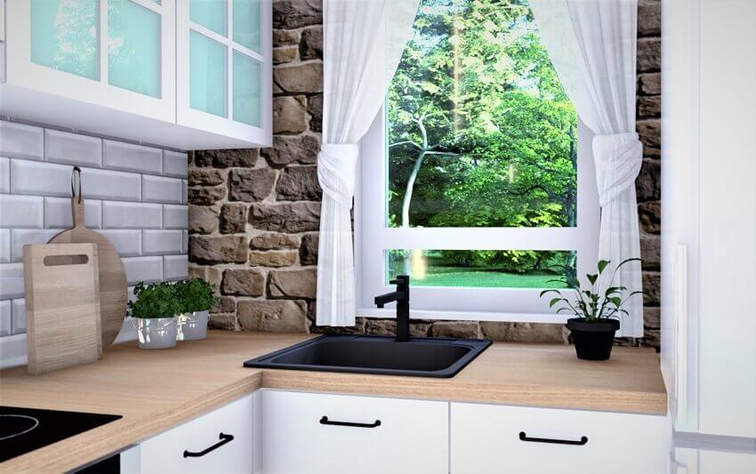 stone wall in kitchen,white kitchen cabinets black sink,kitchen with window over sink,dizajn kuhinje sa dnevnim boravkom,kuća za odmor u prirodi,