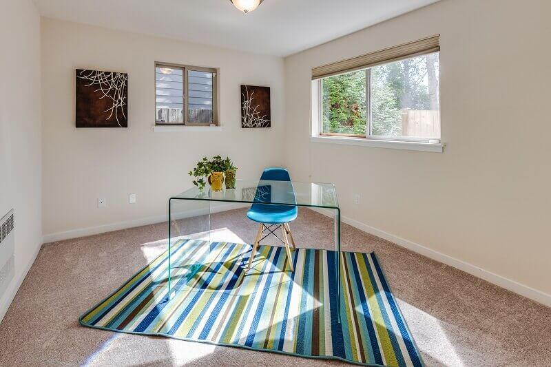 home office in blue colour combination,colorful rug in home office area,blue work chair,transparent work desk,colors decor for home office flooring,