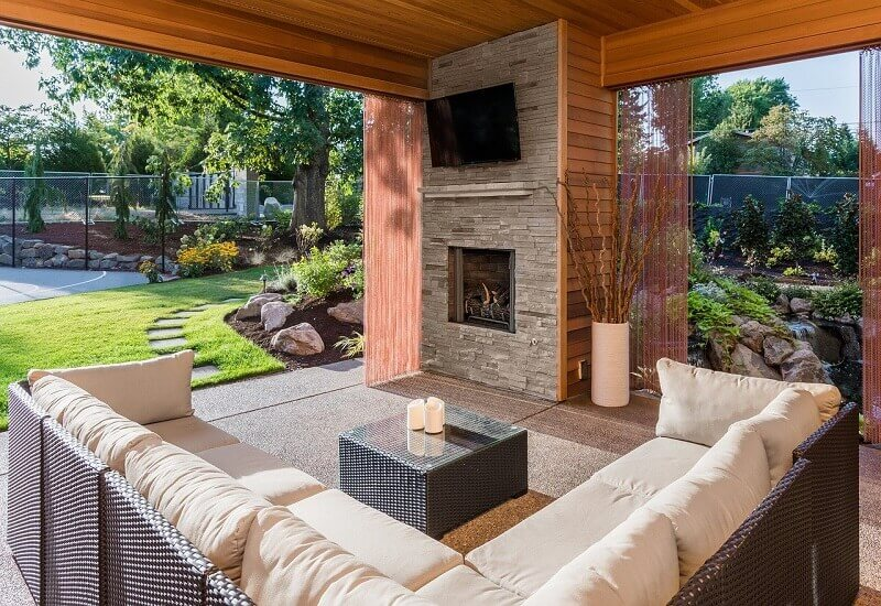 stone and wood wall design outside,outdoor living room with fireplace,corner sofa for garden,outdoor living space with tv,covered outdoor living spaces,