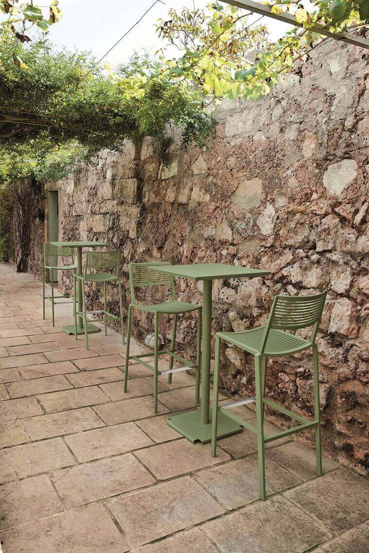 outdoor workspace ideas,mediterranean stone wall images,green outdoor bar height table and chairs,green outdoor furniture design,natural color exterior design ideas,