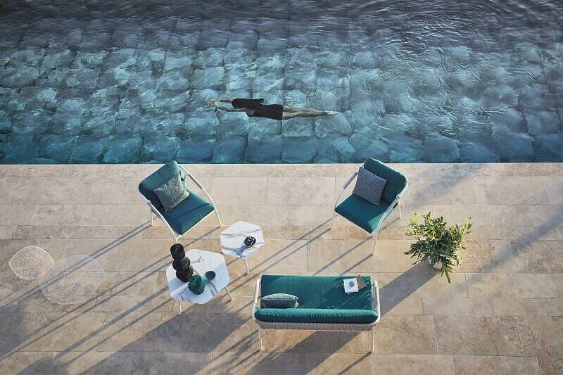 designer poolside ideas,woman swimming in pool,capri inspired decor,blue and white outdoor furniture,small loveseat outdoor furniture,