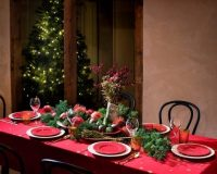 red tablecloth with white snowflakes,table centerpiece made of branches and vegetables,red plates for the festive table settings,holiday dinner party ideas,traditional green and red decorating ideas,