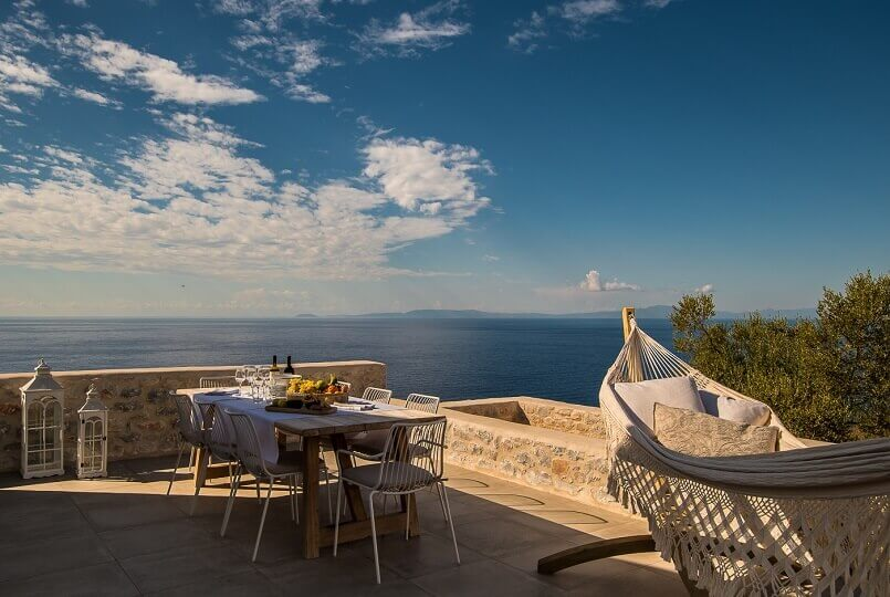 stone terrace decorated in neutral tones,terrace with a view greece,how to create an outdoor dining area,dining space on the terrace,relaxing hammock on the terrace,