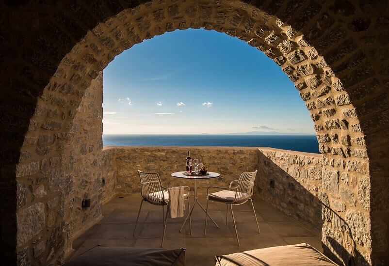 dining space on the terrace,outdoor seating for a couple,stone terrace decorated in neutral tones,terrace with a view greece,how to create an outdoor dining area,